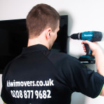 Handyman drilling TV on to the wall