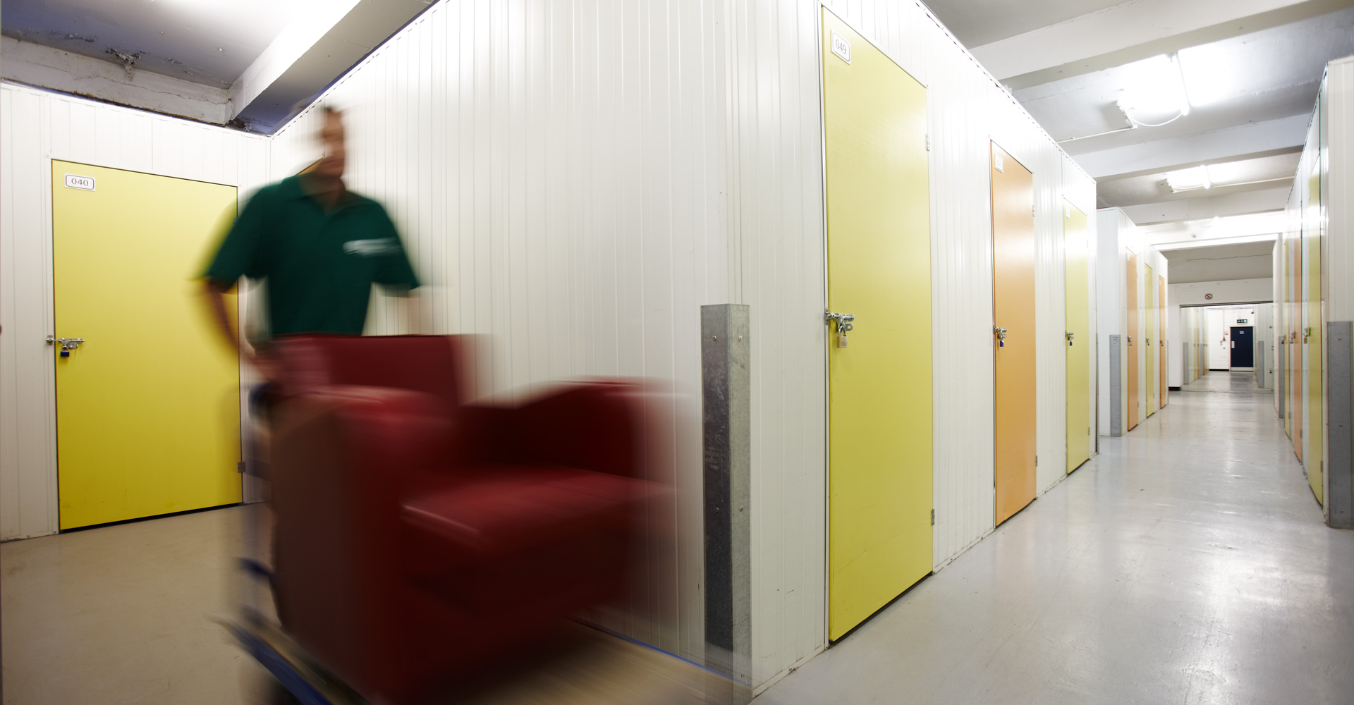 Removal man inside storage unit moving a sofa